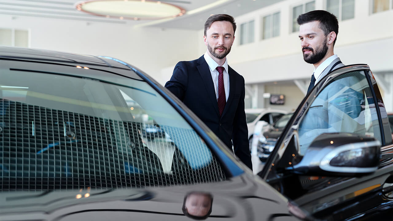 Dois homens analisando um carro