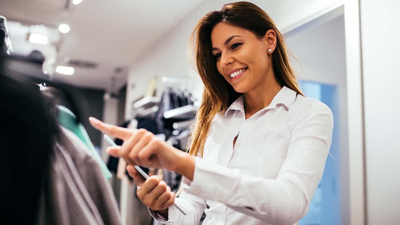 mulher conferindo estoque de roupas