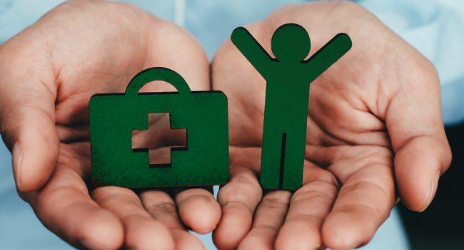 Mãos segurando figuras que representam seguro saúde e vida